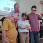 A head and shoulders picture of Reverand Kieran Banks praying over 3 of headlands church leadership
